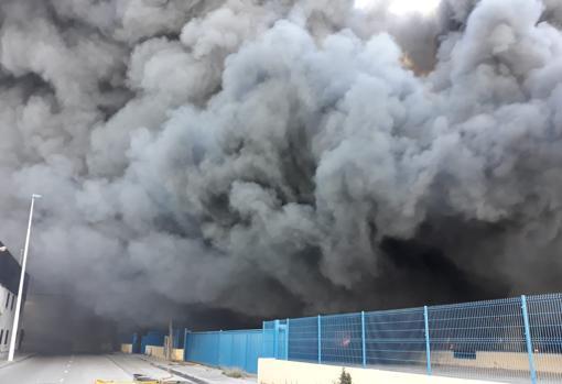 columna de humo del incendio declarado en una empresa próxima al aeropuerto, en el polígono industrial La Cova de Manises