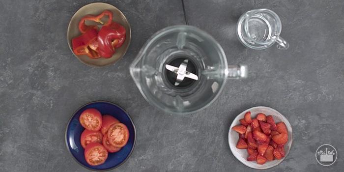 Poner los fresones, los tomates, el pimiento, el agua, la sal y la pimienta negra en latrituradora.